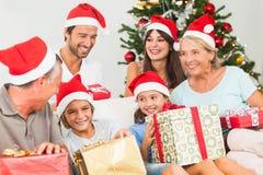 Famiglia felice a natale che cambia i regali Immagini Stock