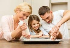 Famiglia felice nel produrre i biscotti a casa fotografie stock