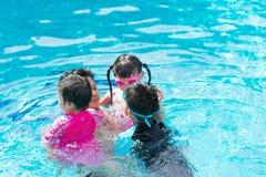 Famiglia felice nella piscina Padre ed i suoi bambini fotografia stock libera da diritti
