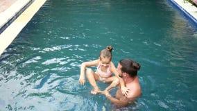 Famiglia felice, padre attivo con il piccolo bambino, figlia adorabile del bambino, divertendosi nella piscina stock footage