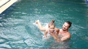 Famiglia felice, padre attivo con il piccolo bambino, figlia adorabile del bambino, divertendosi nella piscina archivi video