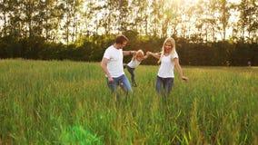 Famiglia felice: Padre, madre e figlio, mantenere nel campo vestito in magliette bianche video d archivio