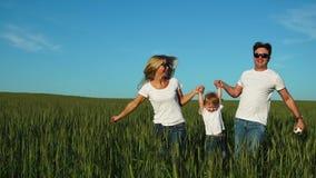 Famiglia felice: Padre, madre e figlio, mantenere nel campo vestito in magliette bianche stock footage