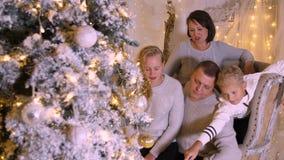 Famiglia felice in salone accogliente sul bello albero di Natale alla vigilia di festa stock footage