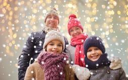 Famiglia felice sopra le luci e la neve di natale Fotografia Stock Libera da Diritti