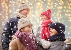 Famiglia felice sopra le luci e la neve di natale Fotografie Stock Libere da Diritti