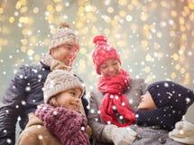 Famiglia felice sopra le luci e la neve di natale Immagini Stock Libere da Diritti