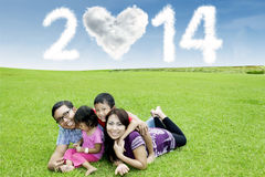 Famiglia felice sotto la nuvola del nuovo anno 2014 Fotografie Stock
