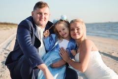 Famiglia felice su una spiaggia ad alba - madre e padre del bambino immagine stock libera da diritti