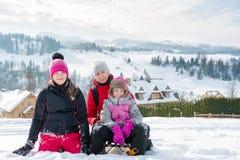 famiglia felice sui precedenti di un paesaggio della montagna di inverno - mamma e figlie su un pendio di collina nevoso in monta immagini stock
