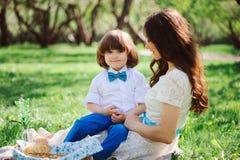Famiglia felice sul picnic per il giorno di madri Figlio del bambino e della mamma che mangia i dolci all'aperto in primavera Immagine Stock Libera da Diritti