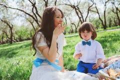 Famiglia felice sul picnic per il giorno di madri Figlio del bambino e della mamma che mangia i dolci all'aperto in primavera Immagine Stock