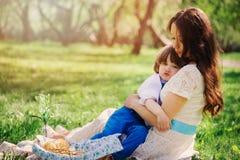 Famiglia felice sul picnic per il giorno di madri Figlio del bambino e della mamma che mangia i dolci all'aperto in primavera o l Immagini Stock