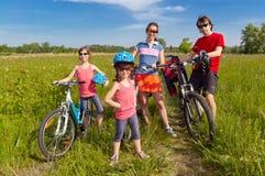 Famiglia felice sulle bici, ciclanti all'aperto Immagine Stock