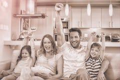 Famiglia felice sullo strato che guarda TV Immagine Stock Libera da Diritti