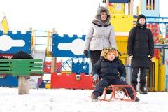 Famiglia felice in un campo da giuoco di inverno dei bambini Fotografia Stock Libera da Diritti