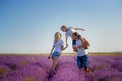 Famiglia felice in un campo di lavanda sul tramonto Fotografie Stock Libere da Diritti