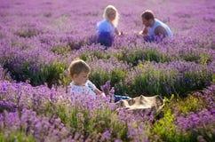 Famiglia felice in un campo di lavanda sul tramonto Immagine Stock