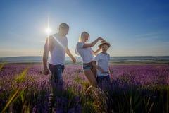 Famiglia felice in un campo di lavanda sul tramonto Immagini Stock Libere da Diritti