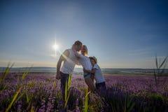 Famiglia felice in un campo di lavanda sul tramonto Fotografia Stock