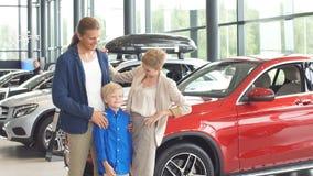 Famiglia felice vicino alla nuova automobile Centro di gestione commerciale automatica video d archivio