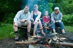 Famiglia felice vicino a fuoco di accampamento Fotografia Stock