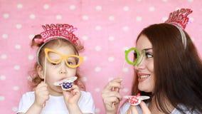 Famiglia - gioco della figlia e della madre insieme, vetri del vestito e di risata e corni di salto Il concetto di una festa, par stock footage