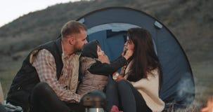 Famiglia giovane bella, a tempo di picnic nella sera accanto della tenda che gioca insieme al tempo divertente del bambino piccol video d archivio