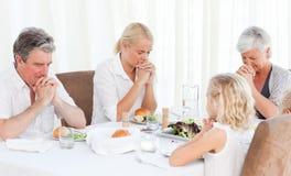 Famiglia graziosa che prega alla tabella Immagine Stock Libera da Diritti