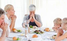 Famiglia graziosa che prega alla tabella Fotografie Stock Libere da Diritti