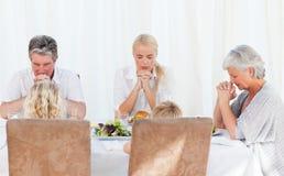 Famiglia graziosa che prega alla tabella Immagini Stock Libere da Diritti