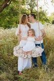 Famiglia incinta felice un giorno di estate sulla natura, sorridendo, famiglia felice Immagine Stock Libera da Diritti