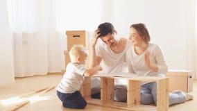 Famiglia insieme al salone della mobilia di montaggio del nuovo appartamento, mucchio delle scatole commoventi su fondo video d archivio