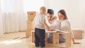 Famiglia insieme al salone della mobilia di montaggio del nuovo appartamento, mucchio delle scatole commoventi su fondo archivi video