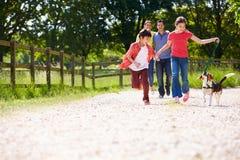 Famiglia ispana che prende cane per la passeggiata in campagna Fotografia Stock