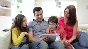 Famiglia ispana che si siede su Sofa With Digital Tablet video d archivio