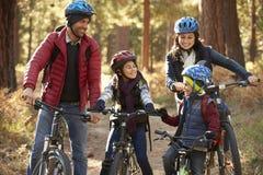 Famiglia ispana sulle bici in una foresta che se esamina immagine stock libera da diritti