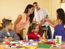 Famiglia ispanica che fa le cartoline di Natale Immagine Stock