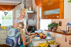 Famiglia - madre che produce prima colazione per la scuola Immagini Stock Libere da Diritti
