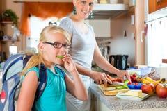 Famiglia - madre che produce prima colazione per la scuola Fotografia Stock