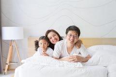 Famiglia, madre, padre felice e figlia asiatici riposanti su w Fotografia Stock Libera da Diritti