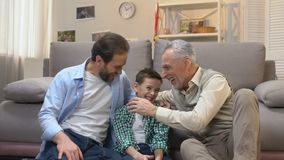 Famiglia maschio felice che ride francamente comunicazione nel salone, generazione stock footage