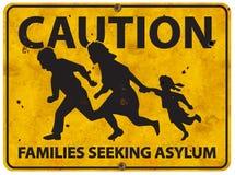 Famiglia messicana del confine che mantene cautela del segno dell'asilo immagini stock libere da diritti