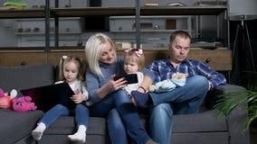Famiglia moderna che per mezzo dei dispositivi astuti di tecnologia