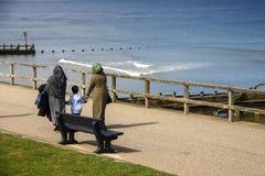 Famiglia musulmana che cammina sulla spiaggia fotografia stock