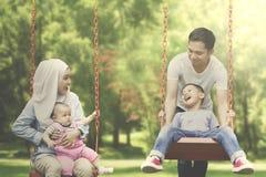 Famiglia musulmana che gioca oscillazione nel parco fotografia stock libera da diritti