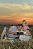 Famiglia nel campo nel tramonto Fotografia Stock