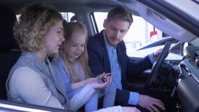 Famiglia nel centro di vendite dell'automobile, mummia e papà sorridente allegro con l'automobile di rassegne della ragazza del b