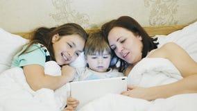 Famiglia nel letto che guarda qualcosa sul computer della compressa video d archivio