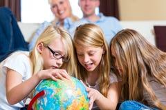Famiglia nel paese, i bambini che giocano con un globo Fotografia Stock Libera da Diritti